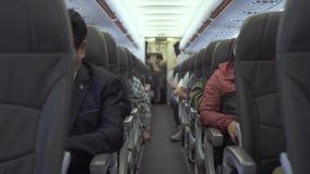Pasajeros que se sientan en los aviones de los asientos mientras que vuela en cielo Pasajeros dentro del vuelo plano comercial de almacen de metraje de vídeo