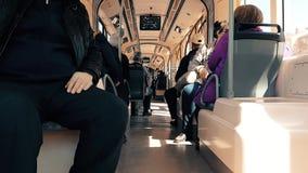 Pasajeros que se sientan en tranvía en el tiempo del día