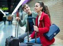 Pasajeros sonrientes jovenes con el tren que espera del equipaje para Fotos de archivo libres de regalías
