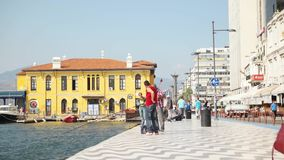 Pasaport ferry station view from land and people fishing and walking at city center stock footage