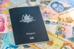 Pasaporte australiano del viaje que miente encima de los billetes de los países diferentes fotografía de archivo libre de regalías
