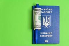 Pasaporte biométrico ucraniano con cientos billetes de dólar y una pluma fotos de archivo libres de regalías