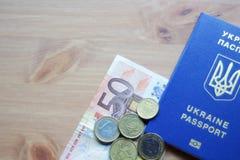 Pasaporte biométrico ucraniano con el billete de banco de cincuenta euros y un manojo de monedas euro fotos de archivo libres de regalías