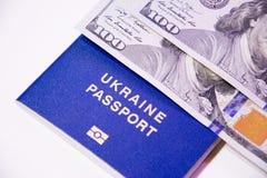 Pasaporte biométrico ucraniano y dos billetes de banco para cientos dólares Foto de archivo