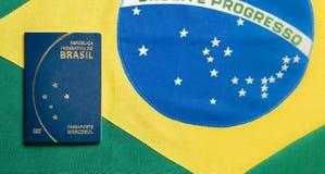 Pasaporte brasileño en fondo brasileño de la bandera fotografía de archivo