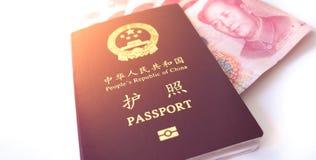 Pasaporte chino con unas notas de Yuan de 100 chinos Imagen de archivo