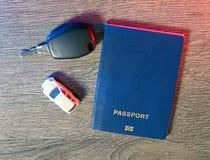 Pasaporte, coche y las llaves al coche a prepararse para el viaje Imagen de archivo libre de regalías
