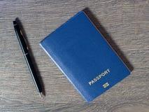 Pasaporte con con la pluma en fondo de madera oscuro Foto de archivo libre de regalías