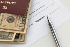 Pasaporte con los billetes de banco y la pluma de los dólares americanos fotografía de archivo libre de regalías