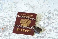 Pasaporte de un ciudadano de la Federación Rusa en una cadena del metal en la cerradura en el fondo del mapa geográfico de Rusia imagen de archivo libre de regalías