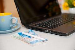 Pasaporte, dinero y ordenador portátil en la tabla de madera Pasaporte ruso Preparación para el recorrido imagen de archivo
