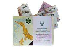 Pasaporte electrónico tailandés con los billetes de banco doblados del baht Imagen de archivo libre de regalías