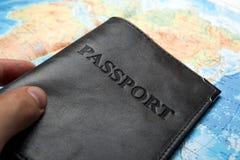 Pasaporte en el bolso en un mapa Imagenes de archivo