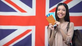 Pasaporte femenino feliz de la tenencia del viajero con los boletos del vuelo contra bandera británica metrajes