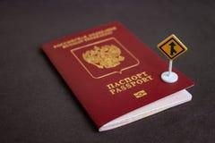 Pasaporte internacional ruso con una señal de tráfico amarilla de la flecha - concepto de la migración fotos de archivo libres de regalías