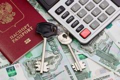 Pasaporte, llaves y la calculadora en un fondo del dinero Imagen de archivo libre de regalías