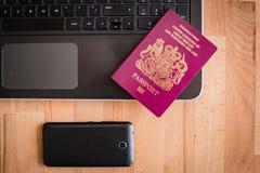Pasaporte, ordenador portátil y teléfono Imagen de archivo