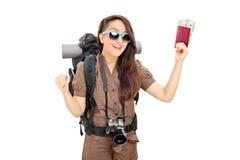 Pasaporte que se sostiene turístico femenino feliz con el dinero Foto de archivo