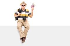 Pasaporte que se sostiene turístico maduro con el dinero Imagenes de archivo