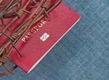 Pasaporte rojo detrás del alambre de púas Imagen de archivo