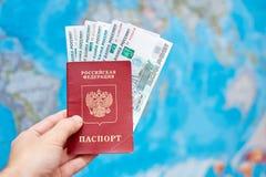 Pasaporte ruso con los billetes de banco de la rublo en el fondo del mapa del mundo Imagen de archivo libre de regalías