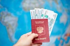 Pasaporte ruso con los billetes de banco de la rublo en el fondo del mapa del mundo Imágenes de archivo libres de regalías