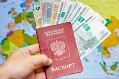 Pasaporte ruso con los billetes de banco y las rublos euro en el fondo del mapa del mundo Fotos de archivo libres de regalías