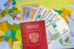Pasaporte ruso con los billetes de banco y las rublos euro en el fondo del mapa del mundo Foto de archivo libre de regalías