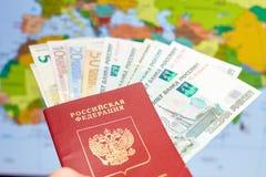 Pasaporte ruso con los billetes de banco y las rublos euro en el fondo del mapa del mundo Imagen de archivo libre de regalías