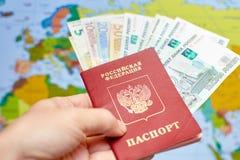 Pasaporte ruso con los billetes de banco y las rublos euro en el fondo del mapa del mundo Foto de archivo