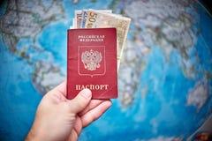 Pasaporte ruso y billetes de banco euro en el fondo del mapa Imagenes de archivo