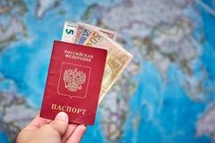 Pasaporte ruso y billetes de banco euro en el fondo del mapa Foto de archivo