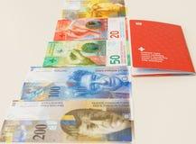 Pasaporte suizo y francos suizos con las nuevas 20 y 50 cuentas del franco suizo Foto de archivo libre de regalías