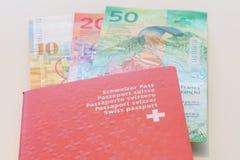 Pasaporte suizo y francos suizos con las nuevas 20 y 50 cuentas del franco suizo Foto de archivo