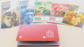 Pasaporte suizo y francos suizos con las nuevas 20 y 50 cuentas del franco suizo Imagenes de archivo