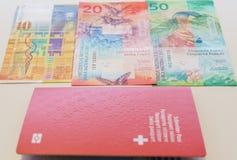 Pasaporte suizo y francos suizos con las nuevas 20 y 50 cuentas del franco suizo Imágenes de archivo libres de regalías