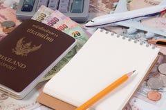 Pasaporte tailandés con el billete de banco tailandés del dinero, la moneda tailandesa y el aeroplano Imagen de archivo libre de regalías