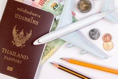Pasaporte tailandés con el billete de banco tailandés del dinero, la moneda tailandesa y el aeroplano Imagen de archivo