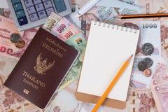 Pasaporte tailandés con el billete de banco tailandés del dinero, la moneda tailandesa y el aeroplano Foto de archivo