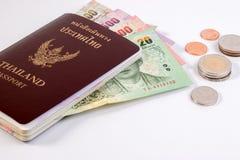 Pasaporte tailandés con el billete de banco tailandés del dinero y la moneda tailandesa aislados en blanco Fotografía de archivo