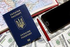 Pasaporte ucraniano en el fondo de las cuentas del ciento-dólar junto con un teléfono y una tarjeta Foto de archivo libre de regalías