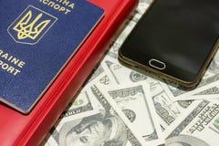 Pasaporte ucraniano en el fondo de las cuentas del ciento-dólar junto con un teléfono y una tarjeta Imágenes de archivo libres de regalías