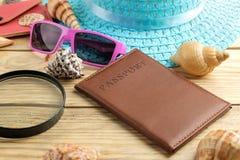 Pasaporte, vidrios, sombrero y cáscaras del concepto del viaje en una tabla de madera natural Relajación holidays fotos de archivo libres de regalías