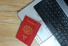 Pasaporte y ordenador portátil Fotografía de archivo libre de regalías