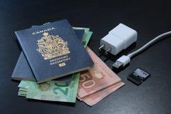 Pasaportes canadienses con los billetes de banco de los dólares canadienses fotografía de archivo