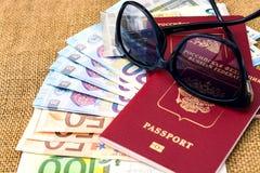 Pasaportes con moneda de la unión europea y gafas de sol en un fondo del mapa concepto del recorrido Imágenes de archivo libres de regalías