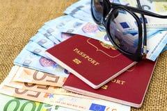 Pasaportes con moneda de la unión europea y gafas de sol en un fondo del mapa concepto del recorrido Imagen de archivo
