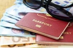Pasaportes con moneda de la unión europea y gafas de sol en un fondo del mapa concepto del recorrido Fotografía de archivo libre de regalías