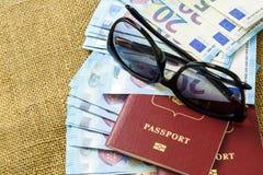 Pasaportes con moneda de la unión europea y gafas de sol en un fondo del mapa concepto del recorrido Imagen de archivo libre de regalías