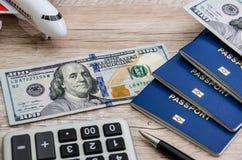 Pasaportes, dólares, calculadora, pluma y avión en un fondo de madera foto de archivo libre de regalías